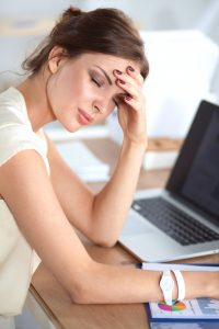 Tired woman sitting at desk, Accurate Acupuncture Chronic Fatigue Syndrome