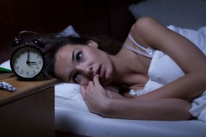 Insomnia patient awake in a bed with a table clock beside the bed