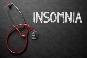 Insomnia treatment written in a blackboard beside a stethoscope