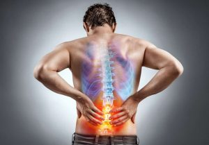 Lower back pain man holding his lower back spine image superimposed